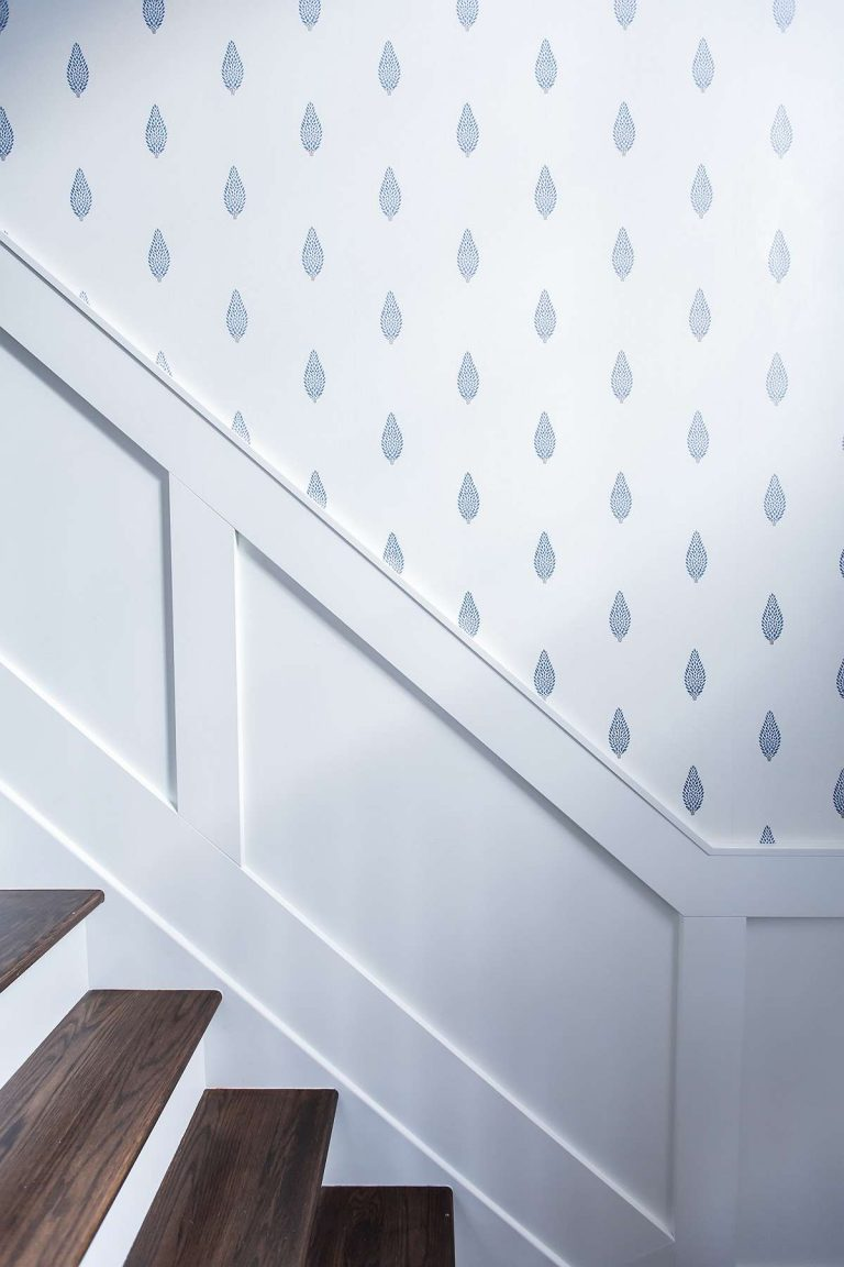Staircase with white wall panelling and blue and white tree patterned wall paper