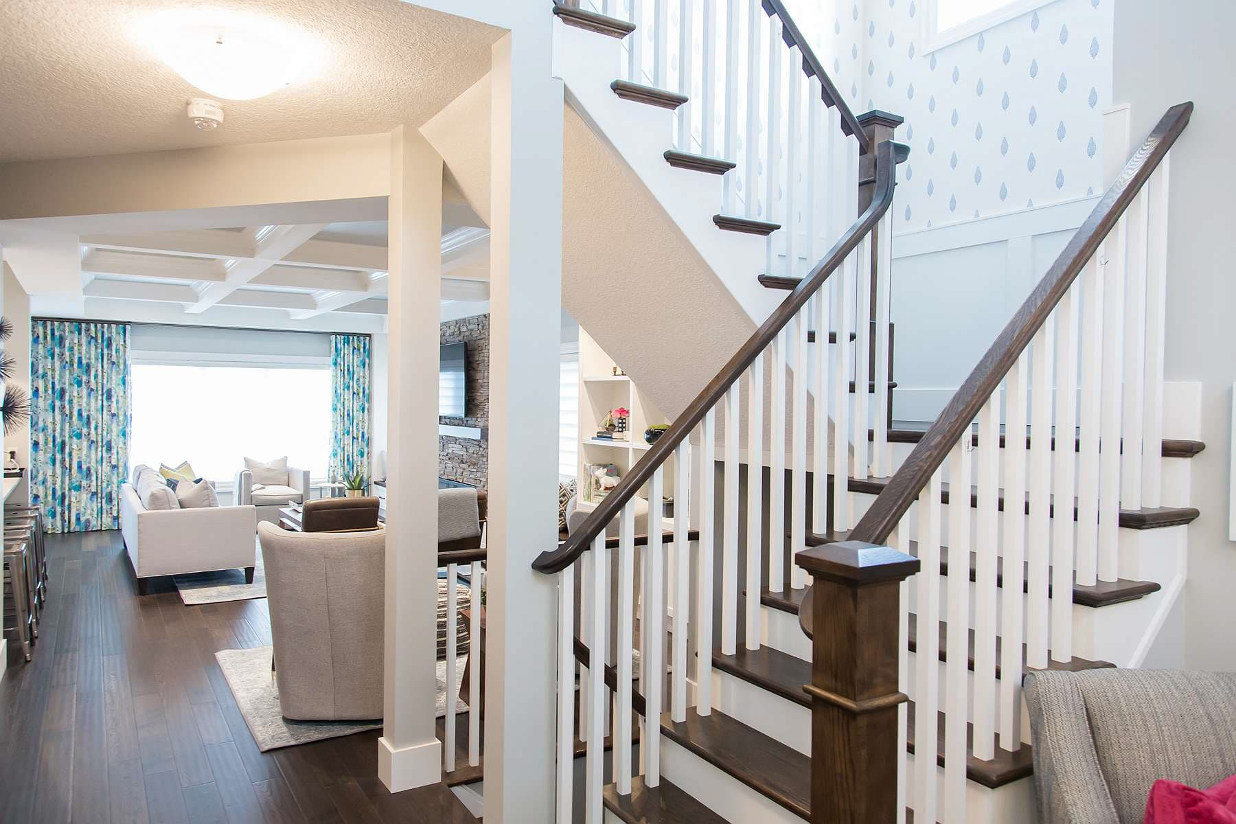 Staircase featuring painted white spindle and risers and wood stained handrail, newal and tread opening into family room with coffered ceiling
