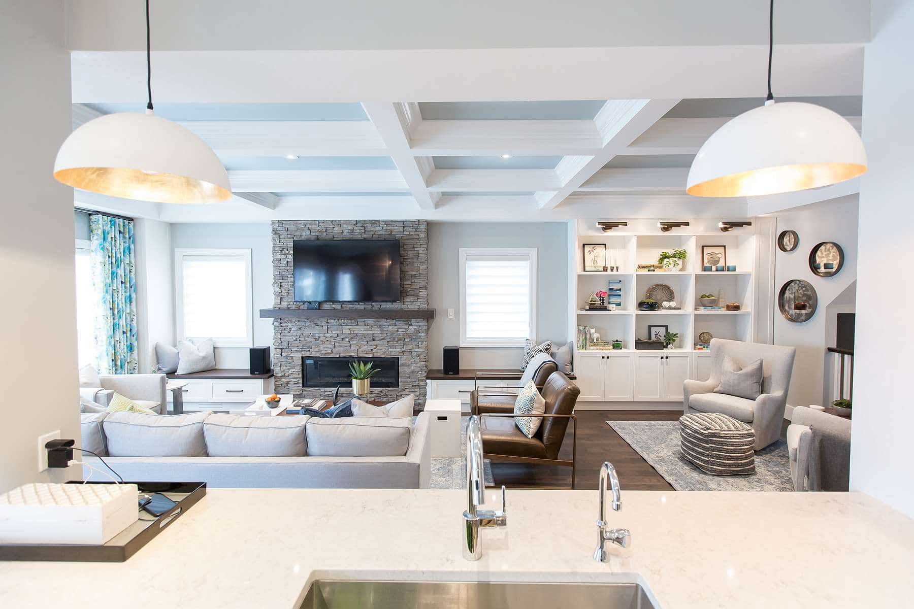 View of Family Room from Kitchen featuring white and gold dome pendant lighting, blue coffered ceiling, stacked stone fireplace and built in wall units