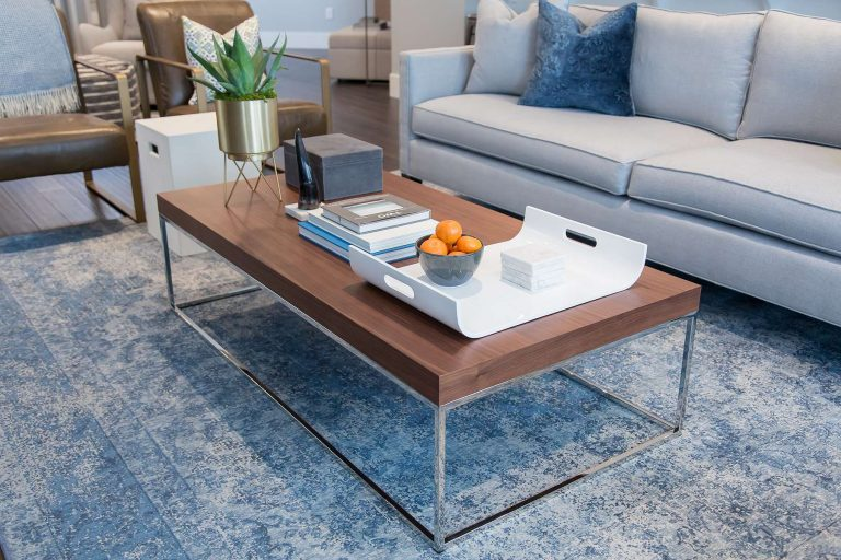 Solid wood coffee table with chrome frame, ivory blue vintage rug and light blue upholstered sofa
