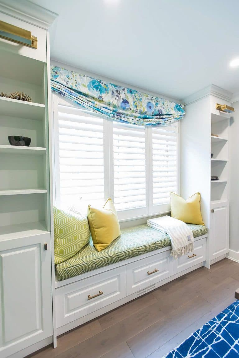 Custom built-in cabinetry with visual comfort brass library lights and custom window seating with Barrow Fabrics and blue floral printed linen lazy roman window valence.