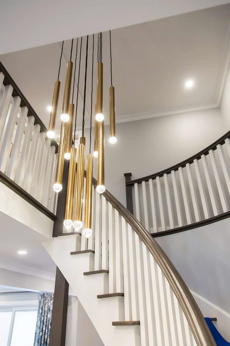 Circular staircase featuring multi drop tubular brass chandelier.