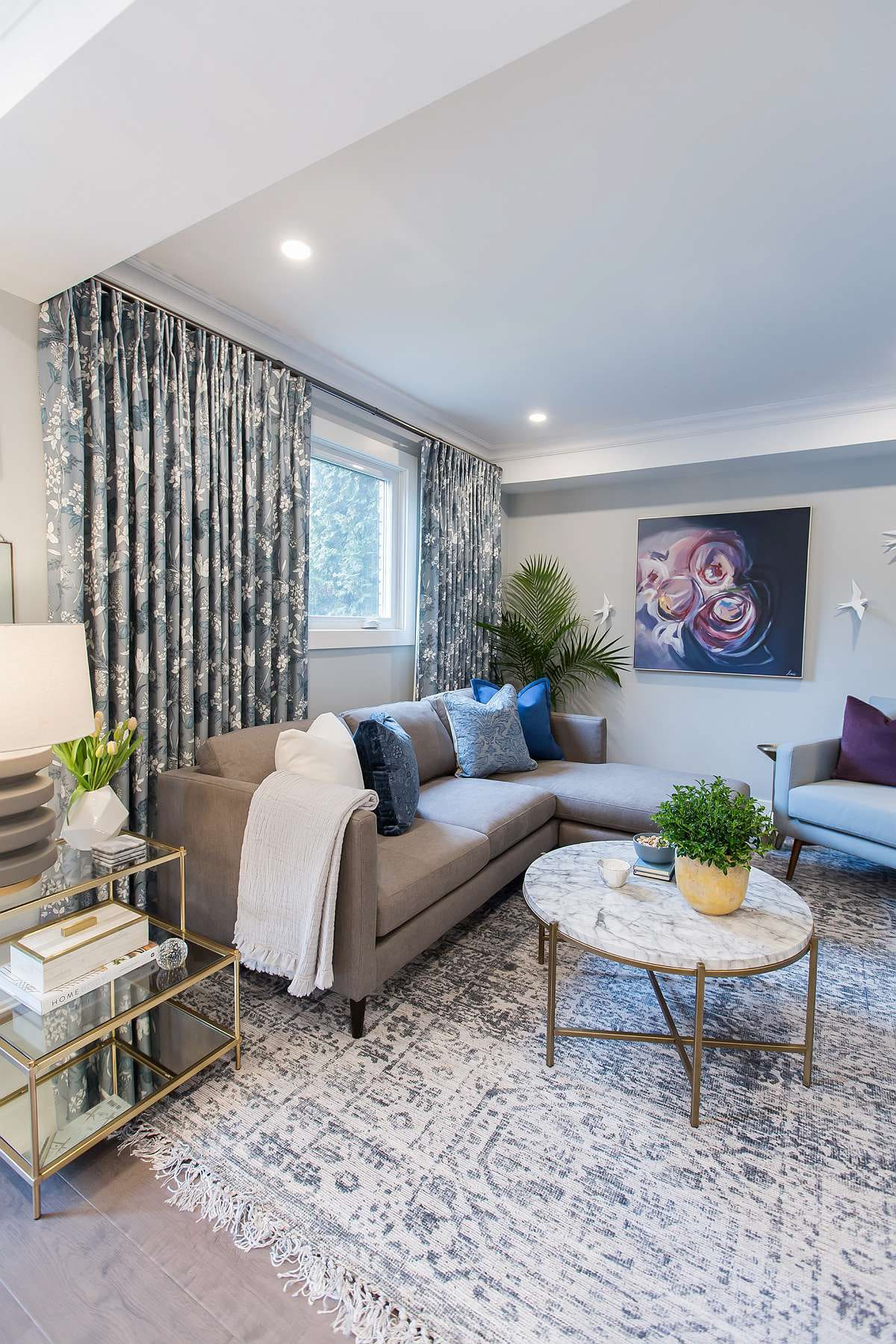 Family room featuring Elte grey sectional and Maxwell fabric vintage floral blue and white custom drapery and marble and brass coffee table and pale blue Nuevo reading chair and grey and blue burnout damask pattern rug and grey flow décor lamp.