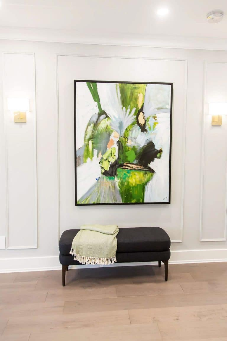 Foyer with wall mouldings and brass wall sconces with linen shades and bench seat and abstract green artwork.