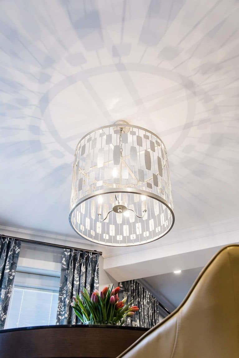 Elongated nickel hex pendant light reflected on ceiling.