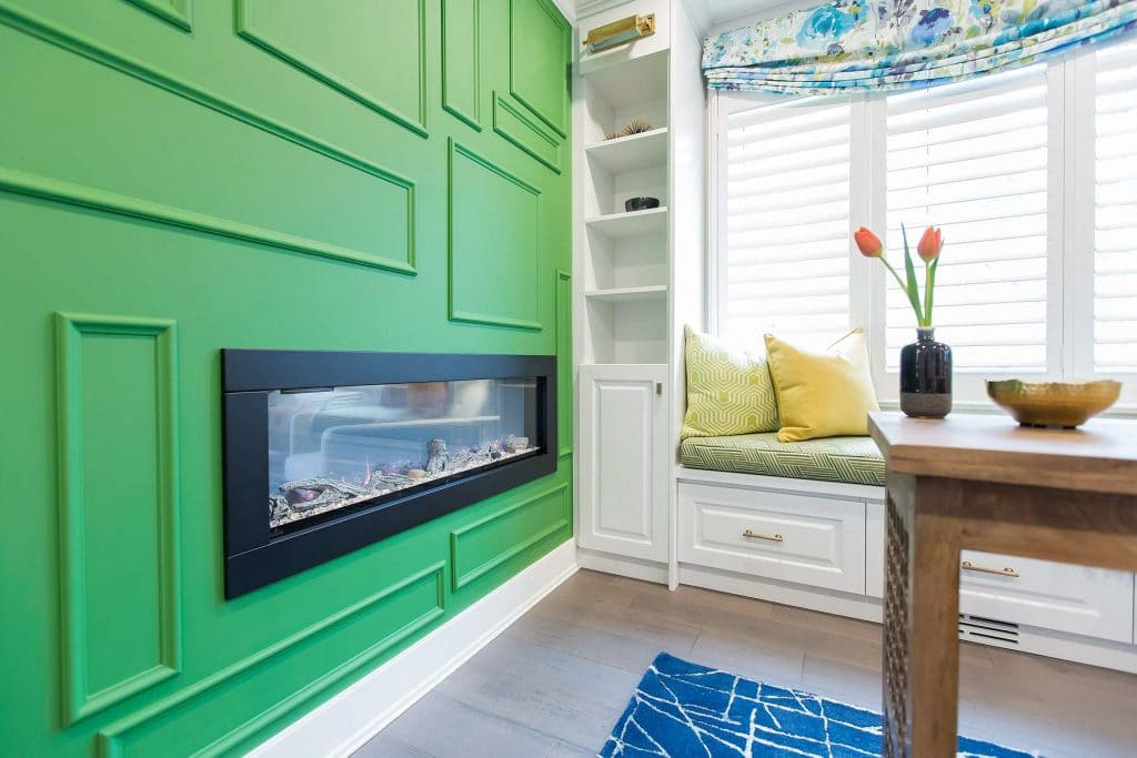 Home office featuring a double-sided fireplace mounted in random framed Kelly green wall with custom built-in cabinetry and custom window seating.