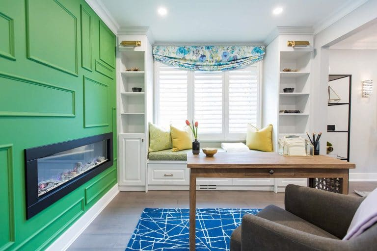 Home office featuring a double-sided fireplace mounted in random framed Kelly green wall with custom built-in cabinetry and custom window seating and Desk with Armchair.