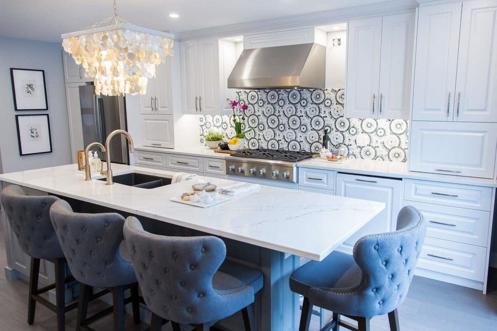 Kitchen island with white and grey quartz top with black undermount granite sink and gold Brizo Litze faucets and grey flannel tufted counter stools and stainless steel Vent-a-hood exhaust and linear capiz shell chandelier with Chantilly lace cabinets.