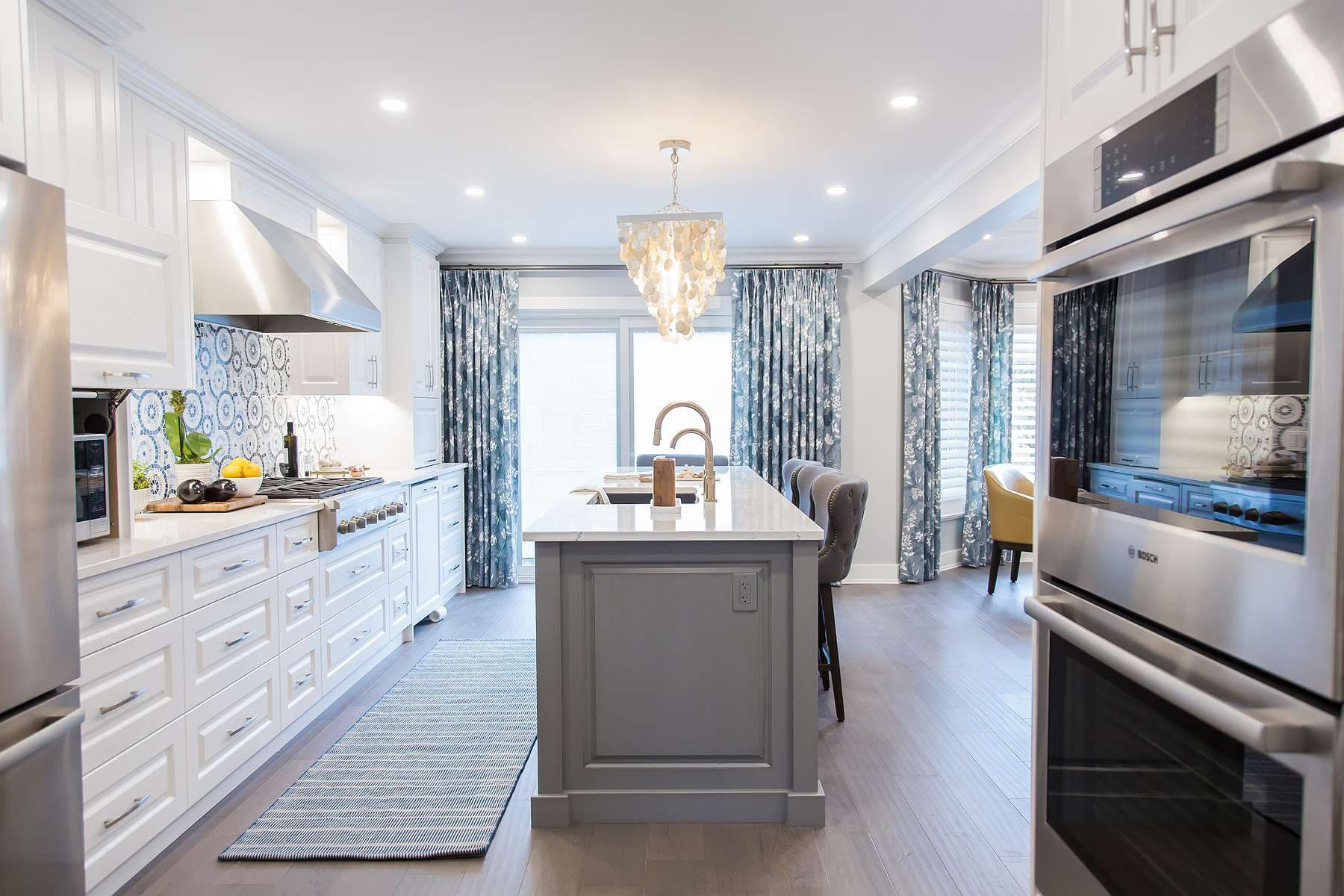 Kitchen island in dark grey with white and grey quartz top with black undermount granite sink and stainless steel Vent-a-hood exhaust and linear capiz shell chandelier with Chantilly lace cabinets and double wall ovens and Dash and Albert Samson blue and natural runner.