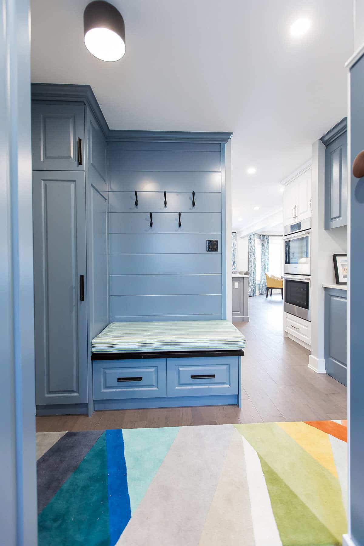 Mudroom with custom medium blue cabinet with bench seat with Redondo beach striped indoor / outdoor fabric and horizontal shiplap and CB2 geometric color block runner.