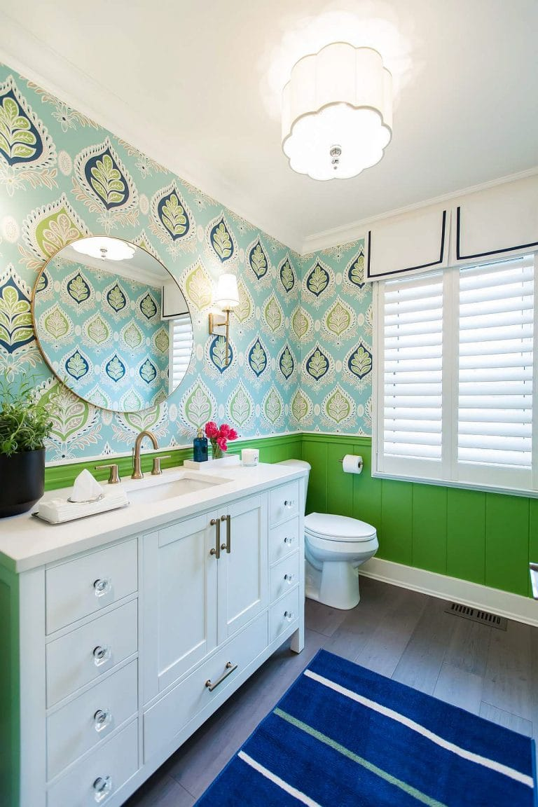 Powder room with Kelly green shiplap lower and upper thibaut geometric floral wallpaper in turquoise, navy blue and kelly green and white cabinets with crystal and gold drawer pulls and round framed mirror and gold wall sconces and custom window valences with navy grosgrain trim.
