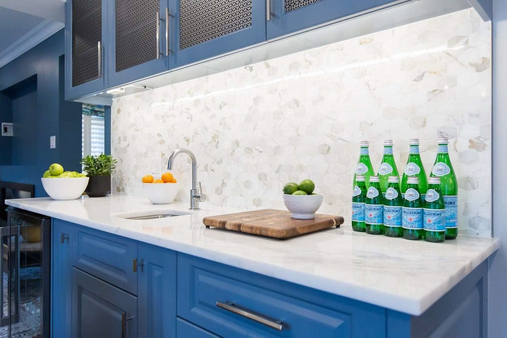 Medium blue kitchen service credenza with hex punched stainless steel insert on upper cabinets and elongated hex cabinet pulls and elongated hex calacatta marble backsplash with an onyx countertop.