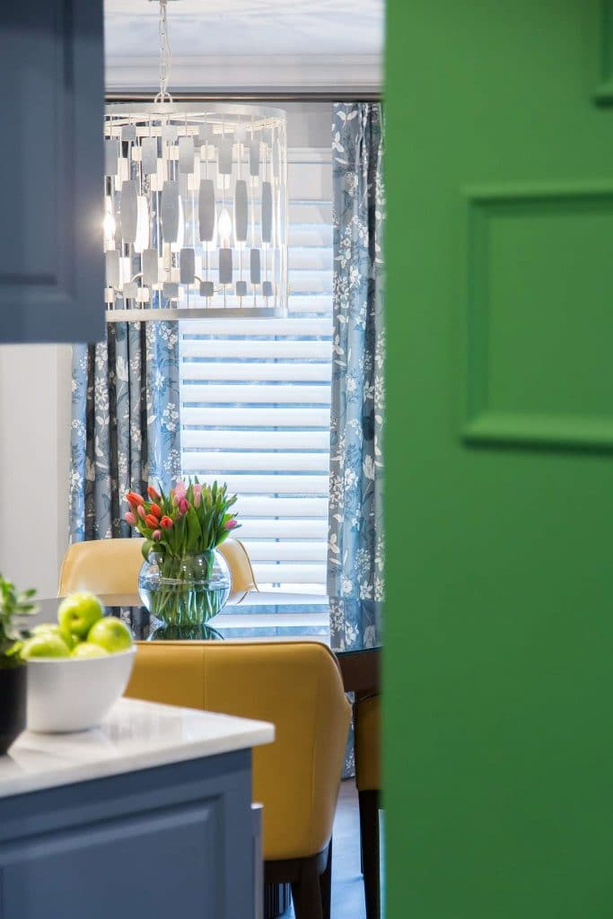 View into kitchenette featuring Kelly green wall and medium blue cabinets with onyx countertop and elongated nickel hex pendant light.