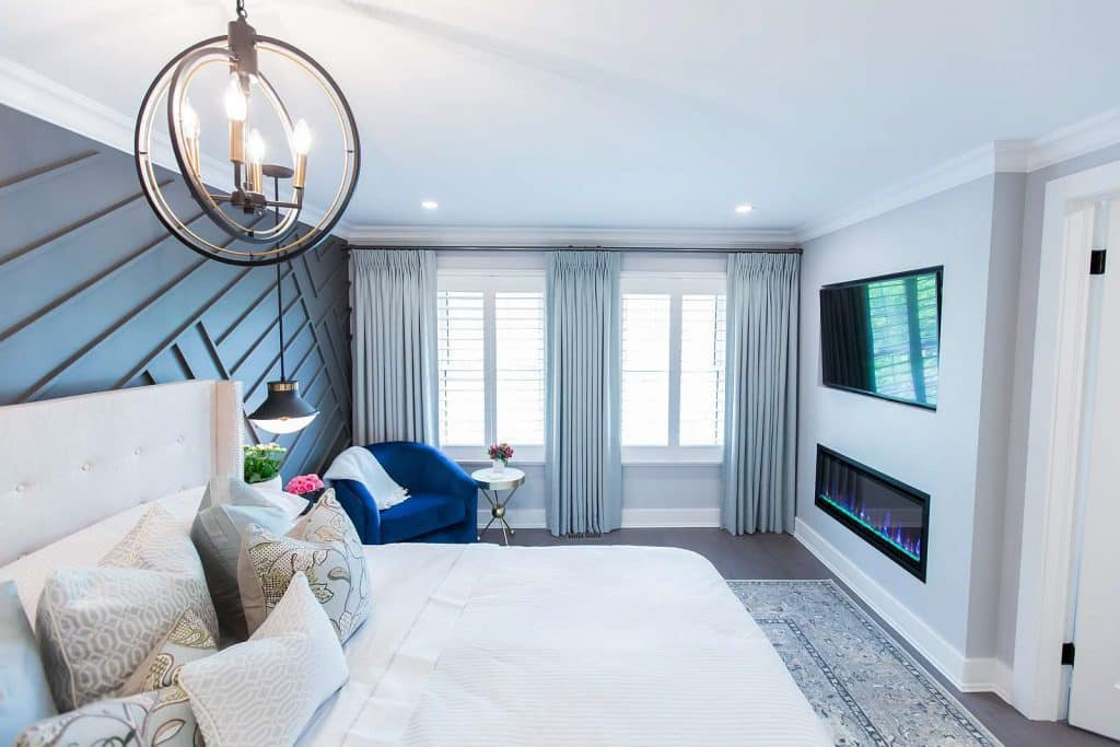 Master bedroom with diagonal wall paneling in Benjamin Moore Flint, Mateo black and brass orb chandelier, custom drapery panels, cotton viscose rug and built-in linear gas fireplace and television