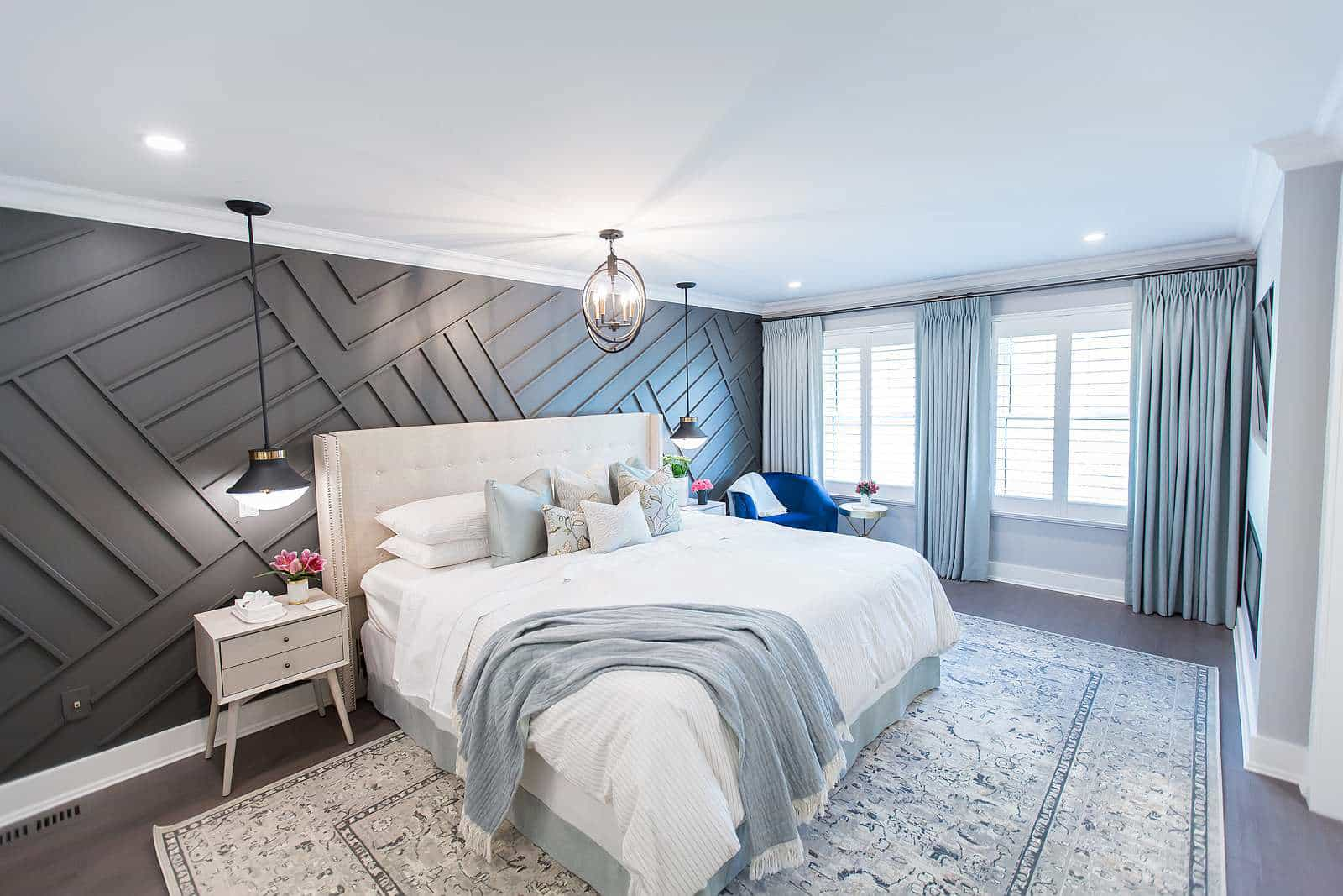 Master bedroom with diagonal wall paneling in Benjamin Moore Flint, Bedside tables with Mateo ceiling-mounted pendant lights and Mateo black and brass orb chandelier, custom drapery panels and cotton viscose rug.
