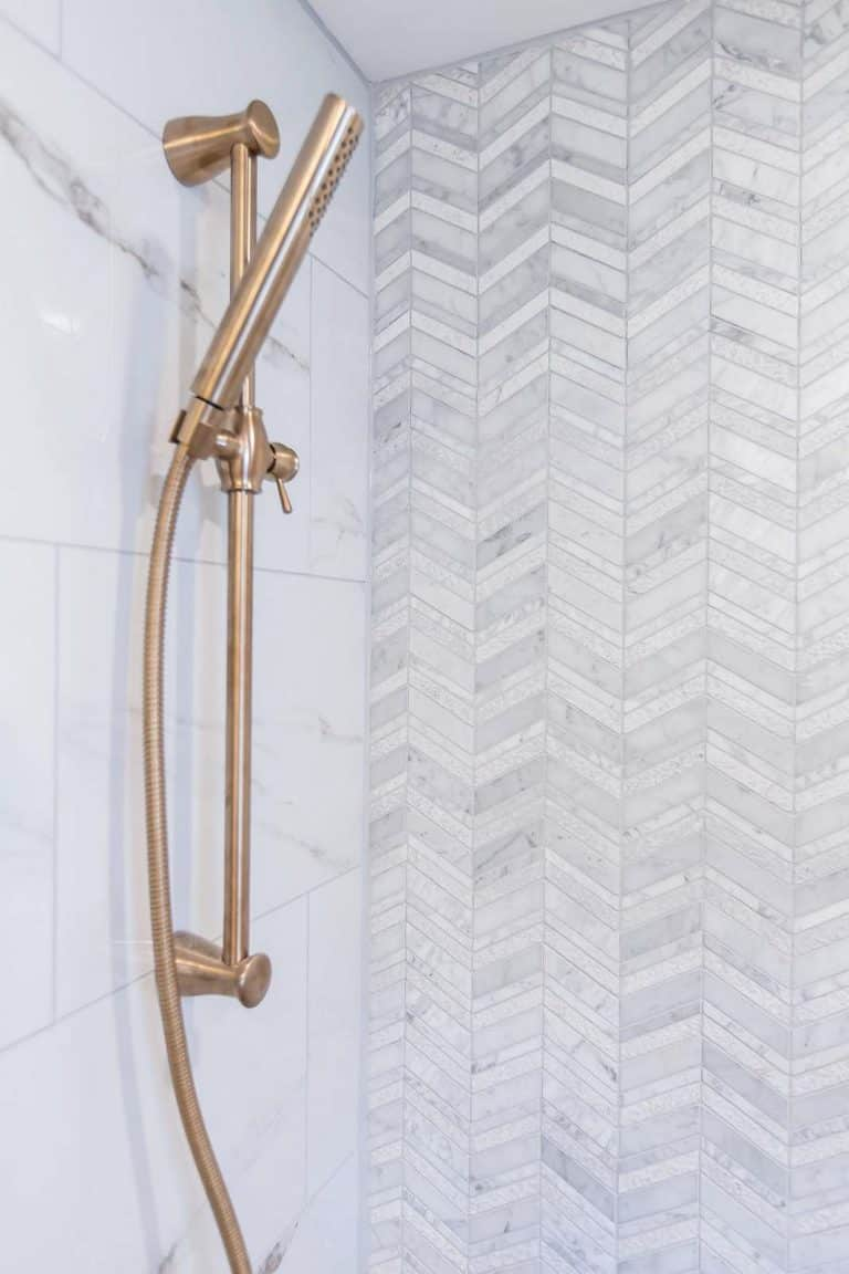 Shower detail with calcutta porcelain tile, chevron marble accent wall tile, delta shower slide bar and shower head in champagne bronze.