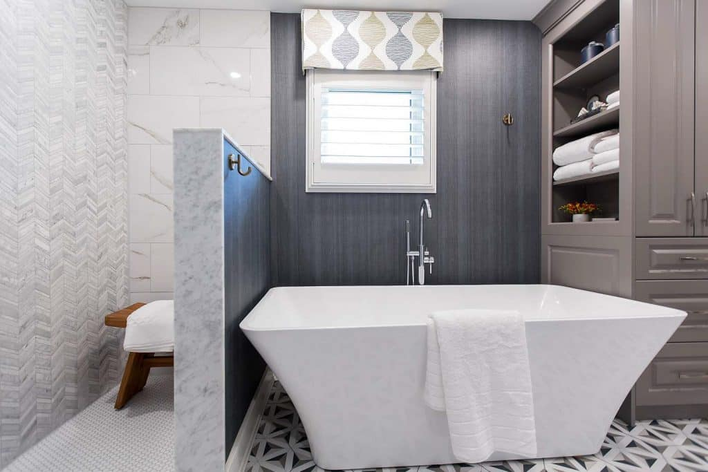 Shower with calcutta porcelain tile, chevron marble accent wall tile, teak wood shower bench, soaker tub, built-in storage tower, Maxwell Fabrics geometric embroidered linen fabric and Woeller Group grasscloth wallpaper.