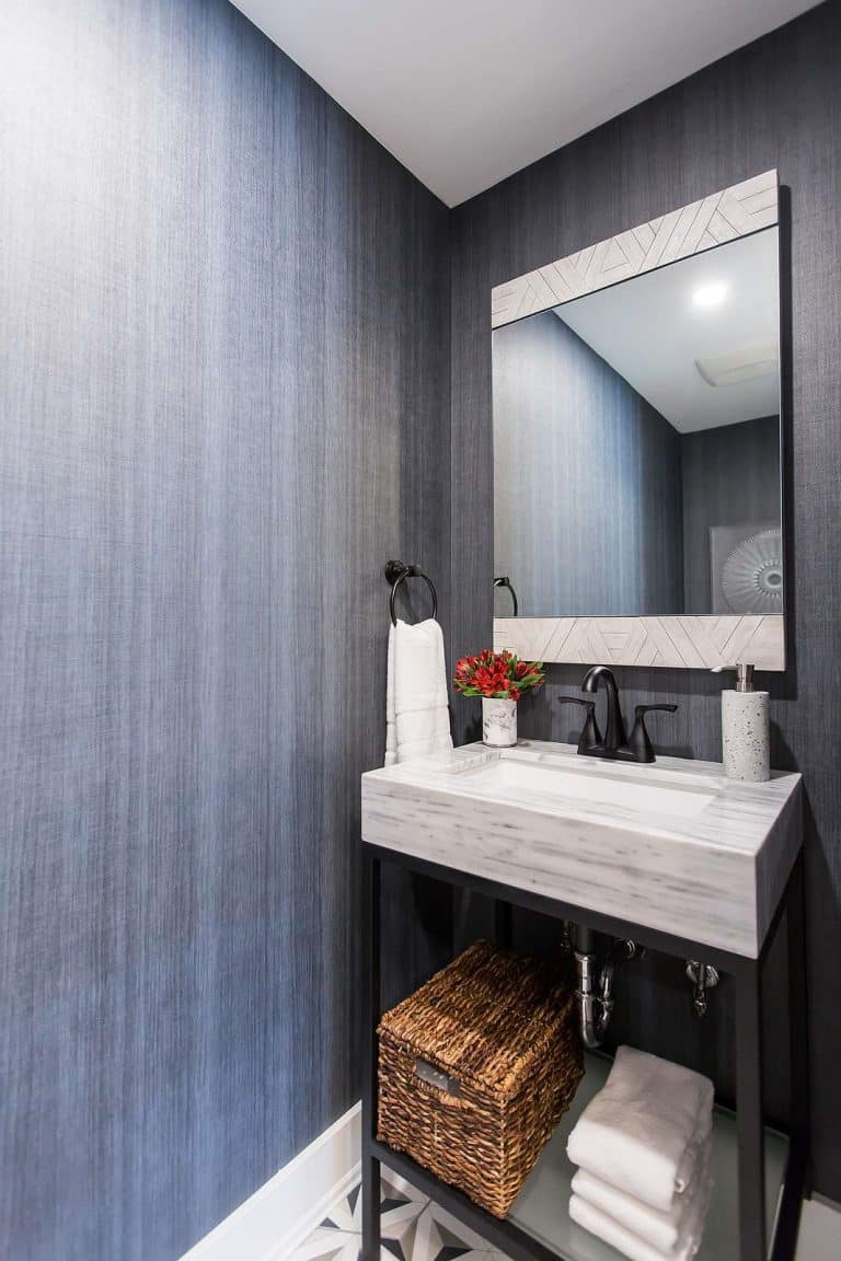 Water closet featuring Woeller Group grasscloth wallpaper and white marble and black metal vanity, black delta faucets and mirror featuring rustic wood in chevron pattern.