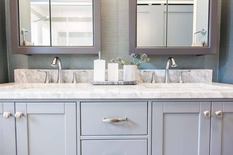 Grey Painted double vanity and Cararra marble counter top and polished chrome faucets and Woeller Group vinyl wall