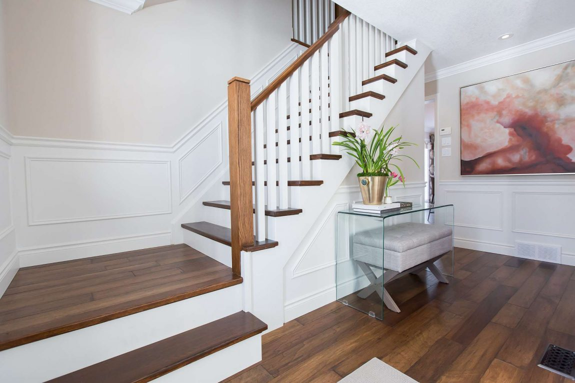 Custom staircase featuring antique hardwood steps, painted white newels and solid wood post with white wall paneling