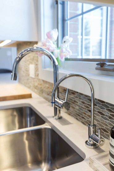 Double stainless steel kitchen sink with chrome taps and warm neutral marble backsplash