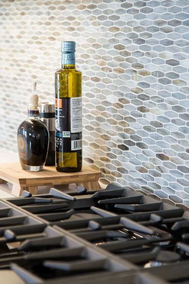 Olive Oil on Wood Chopping Block with gas burner stove and warm neutral marble backsplash