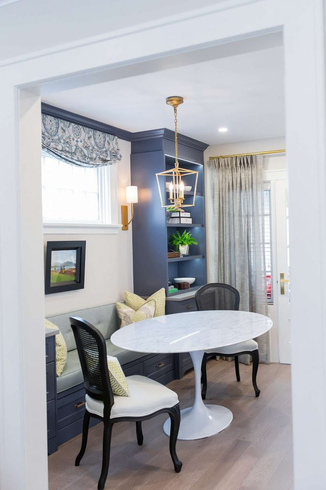 Dining room feature banquette seating with under seat drawers and marble oval dining room table on oak hardwood floor