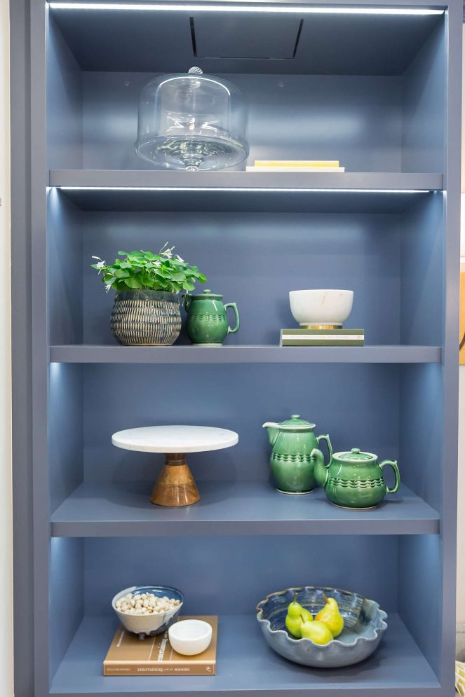 Lacquered grey blue cabinet with open shelving with books, bowls, ceramics and glass