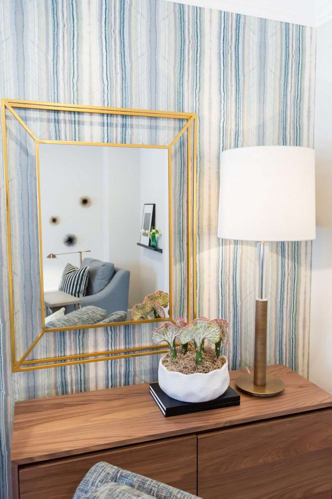 Living room chest and gold leaf architectural mirror with rubbed bronze base and glass stem table lamp