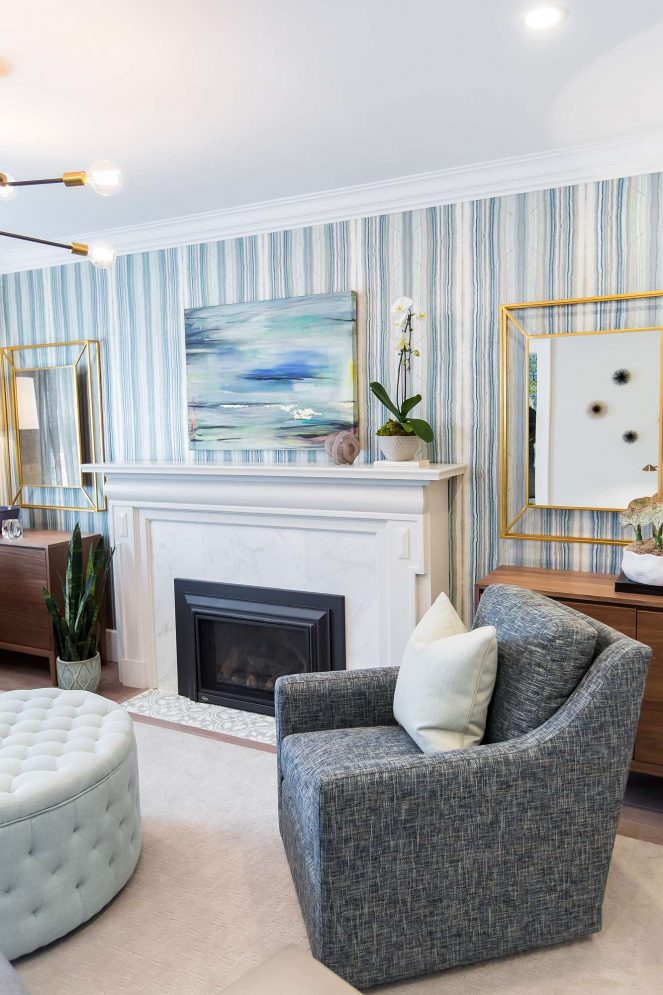 Living room featuring blue and white upholstered arm chair, light blue tufted automan, gas fireplace with marble surround and tile apron, and matching wood cabinets with mirrors