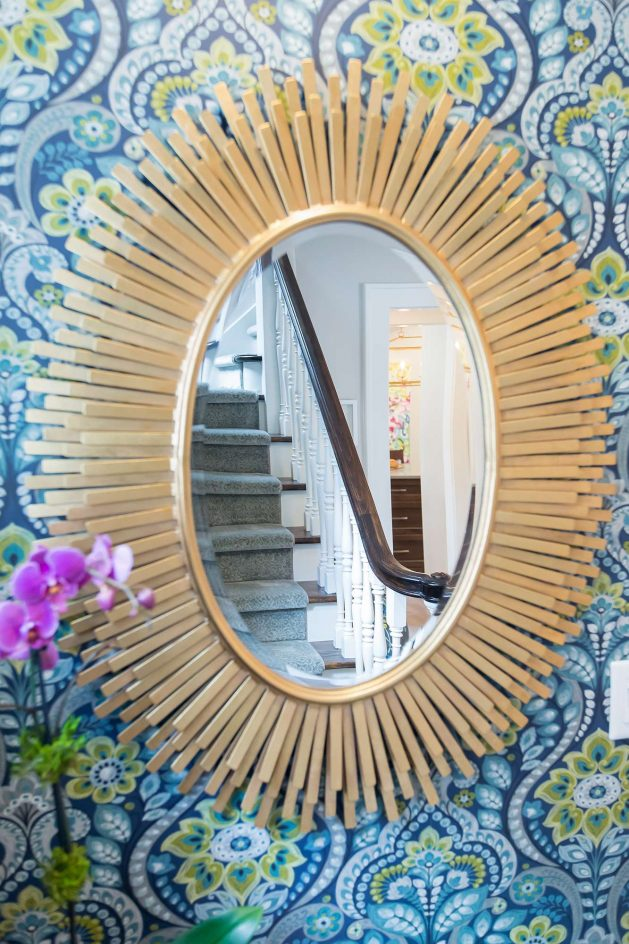 Gold leaf oval mirror on blue and green floral wallpaper