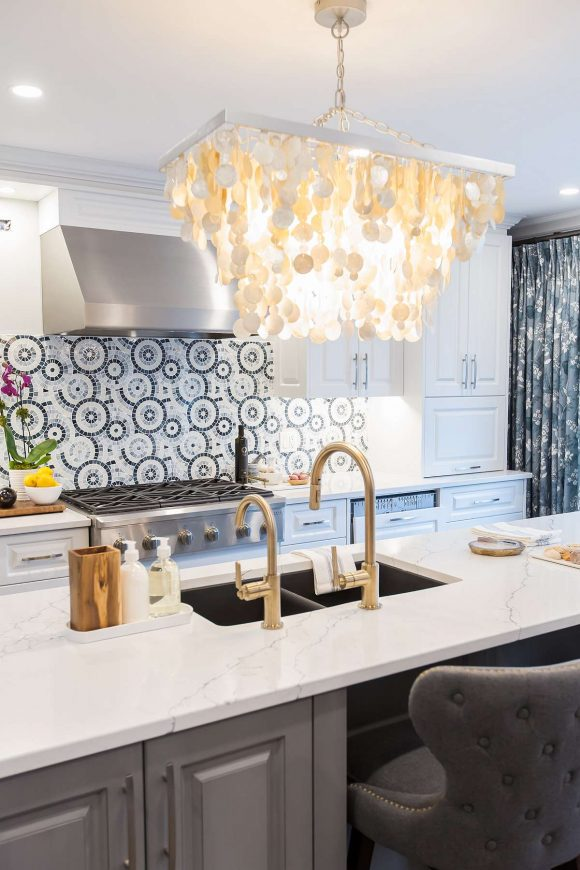 Kitchen island in dark grey with white and grey quartz top with black undermount granite sink and gold Brizo Litze faucets and grey flannel tufted counter stools and stainless steel Vent-a-hood exhaust and linear capiz shell chandelier with Chantilly lace cabinets.